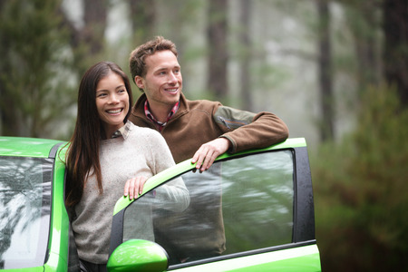 rent car: Driving in car - driver couple resting looking in forest taking break in green rental cars during during road trip travel vacation holiday in beautiful landscape nature. Asian woman, Caucasian man.