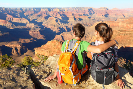 south kaibab trail: Hiking hikers in Grand Canyon enjoying view of nature landscape. Young couple relaxing during hike wearing backpacks on South Kaibab Trail, south rim of Grand Canyon, Arizona, USA. Stock Photo