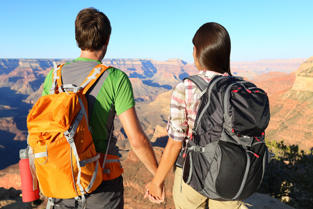 Couple holding hands looking at Grand Canyon. Romantic hikers enjoying view and romance while hiking Grand Canyon, USA. photo
