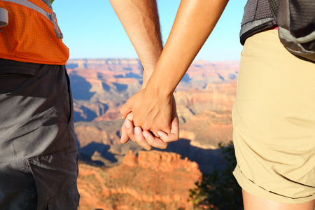 lovers holding hands: Romantic hiking couple holding hands, Grand Canyon. Close up of young lovers on hike enjoying view and romance. Woman and man hikers.
