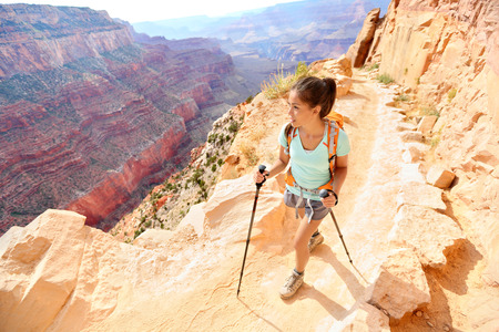Hiker woman hiking in Grand Canyon walking with hiking poles. Healthy active lifestyle image of hiking young multiracial female hiker in Grand Canyon, South Rim, Arizona, USA. Stock Photo