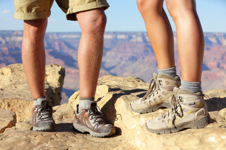 Hiking shoes on hikers in Grand Canyon. Man and woman hiker hike boots in closeup with breathtaking view of Grand Canyon in the background. Male and female feet. photo