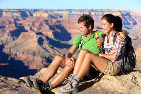 grand canyon: Hiking couple portrait - hikers in Grand Canyon enjoying view of nature landscape smiling happy. Young couple trekking, relaxing after hike on south rim of Grand Canyon, Arizona, USA. Man and woman.