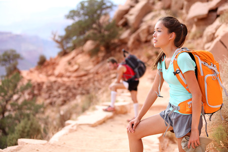 south kaibab trail: Hiker in Grand Canyon. Hiking woman and man resting tired enjoying hike and view on South Kaibab Trail, south rim of Grand Canyon, Arizona, USA. Stock Photo