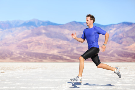 fitness goal: Man running outdoor sprinting for success. Male fitness runner sport athlete in sprint at great speed in beautiful landscape in desert.