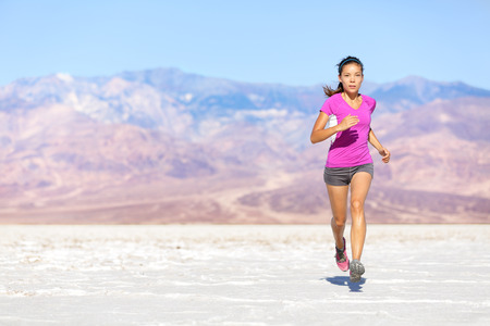 Running sport athlete woman sprinting in trail run in desert. Female fitness runner in sprint workout training in shorts and t-shirt. Fit muscular girl sport model outside under blue sky. photo