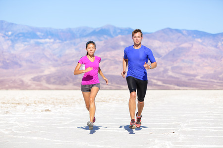 Fitness sport couple running jogging outside on trail in desert landscape.