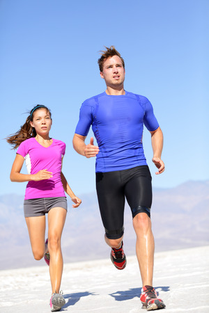 Marathon running athletes couple training in desert. Fitness sport runners living active lifestyle. Fit sports couple, Asian woman, Caucasian man. photo