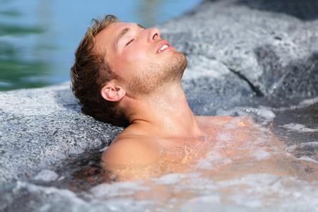 Wellness Spa - ein Mann Entspannung in heißen Wanne Jacuzzi-Whirlpool im Freien am Luxus-Resort Spa Retreat Handsome junge männliche Modell mit den Augen entspannt geschlossen ruhen im Wasser in der Nähe von Pool zu Reisen urlaub