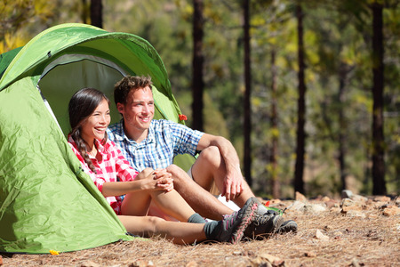 Camping couple in tent sitting looking at view in forest  Campers smiling happy outdoors in forest  Happy multiracial couple having fun relaxing after outdoor activity  Asian woman, Caucasian man Stock Photo