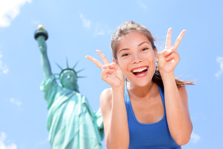 statue of liberty: Tourist at Statue of Liberty, New York, USA making funny face expression victory hand signs excited and happy  Tourism and travel concept with joyful mixed race Asian Caucasian woman