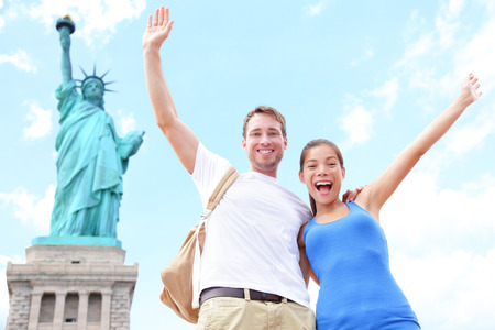 liberty: Travel tourists couple at Statue of Liberty, New York City, USA  Multiracial tourist couple on summer vacation holidays cheering celebrating happy  Asian woman, Caucasian man