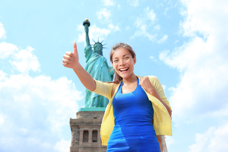 liberty island: New York City Statue of Liberty Tourist woman giving thumbs up  Happy girl on tourism travel on Liberty Island, USA  Young multiethnic woman traveling having fun  Asian Caucasian woman  Stock Photo