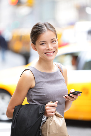 Business woman portrait with smart phone in New York City, Manhattan walking in dress suit holding doggy bag smiling  Young multiracial Asian Caucasian professional female businesswoman in her 20s  Stock Photo