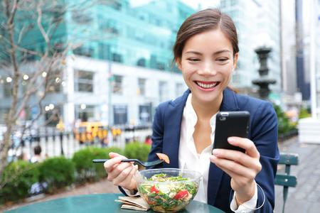 Junge Unternehmen Frau essen Salat auf Mittagspause im Stadtpark lebenden gesunden Lebensstil arbeiten Smartphone Glücklich lächelnde multirassischen junge Geschäftsfrau, Bryant Park, Manhattan, New York City, USA