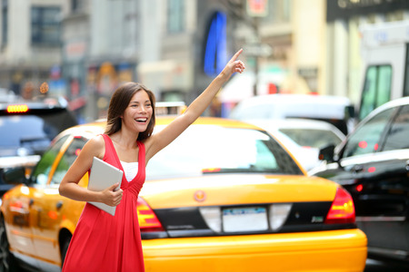 Girl calling taxi cab in New York City, holding tablet pc computer standing in cute summer dress in street of Manhattan, USA  Beautiful young mixed race Asian Caucasian woman outdoor  Stock Photo