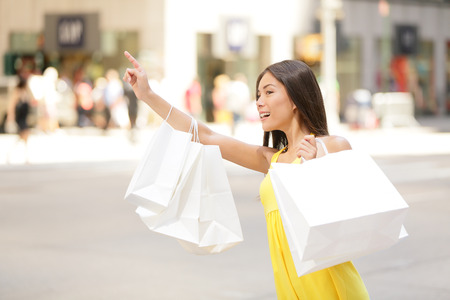 Shopping woman in New York City looking for yellow taxi cab  Beautiful happy summer shopper holding shopping bags walking outside smiling  Multiracial Asian Caucasian model on Manhattan, USA