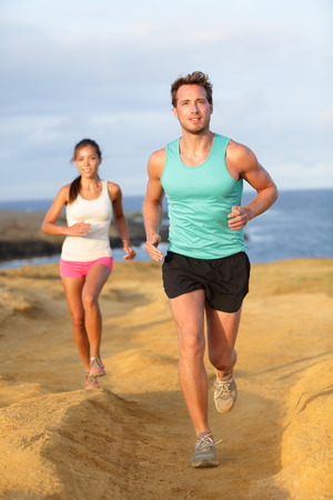 Runners couple jogging for fitness running in beautiful landscape nature outdoors. Young female and male sports athletes training cross-country trail running. Asian woman, Caucasian man, Stock Photo