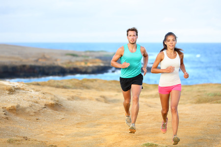 Sports couple jogging for fitness running in beautiful landscape nature outdoors. Young female and male sports athletes training cross-country trail running. Asian woman, Caucasian man, photo