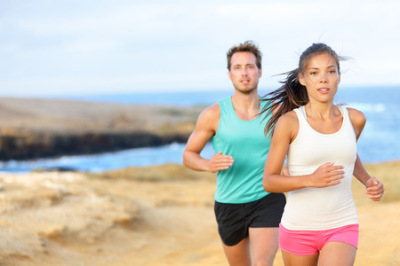 People jogging for fitness running in beautiful landscape nature outdoors. Woman and man sports athletes training cross-country trail running. Couple together, Asian woman, Caucasian man, Stock Photo