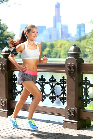 armband: Running woman jogging to music in New York City, Central Park, Manhattan. Runner wearing earphones and armband for smart phone. Female fitness jogger training outside for healthy lifestyle.