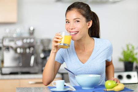 comiendo cereal: Mujer que bebe el zumo de naranja de comer el desayuno que sonríe feliz en la mañana. Mujer multirracial joven sentada en su cocina en casa. Raza mixta modelo asiático mujeres de raza caucásica de comer sano.