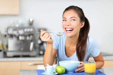 女性朝テーブルの幸せな笑顔と朝の新鮮な朝食用シリアルを食べるします。美しい若い多民族女性の自宅で彼女のキッチンで座っています。混合レ