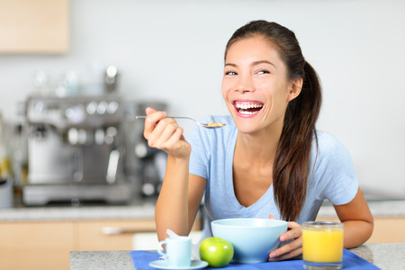 comiendo cereal: Mujer comiendo cereales para el desayuno en la mesa de la mañana fresca sonrisa feliz y mañana. Mujer multirracial joven sentada en su cocina en casa. Modelo femenino de raza mixta asiática del Cáucaso.
