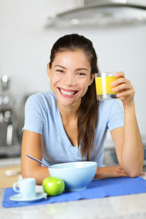 Woman drinking orange juice eating breakfast smiling happy looking at camera in the morning. Beautiful young multiracial woman in kitchen at home. Mixed race Asian Caucasian girl eating healthy photo