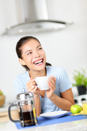 brewing: Woman drinking coffee having breakfast at home at kitchen table laughing happy. Beautiful morning fresh mixed race Asian Caucasian girl in her 20s. Stock Photo