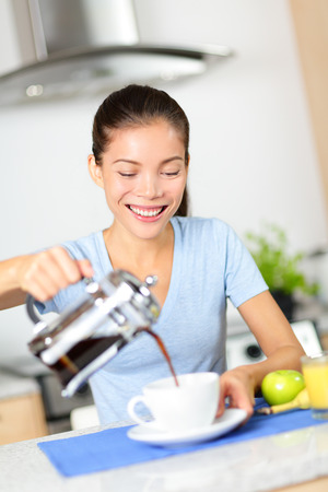 french model: Woman eating breakfast and drinking coffee in the morning. Girl pouring coffee from french press at home in kitchen. Beautiful mixed race Asian Caucasian female model smiling happy.