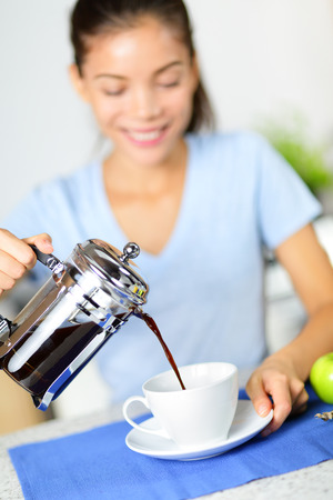 french model: Coffee - woman drinking french press coffee at breakfast table in the morning. Girl pouring black coffee at home in kitchen. Stock Photo