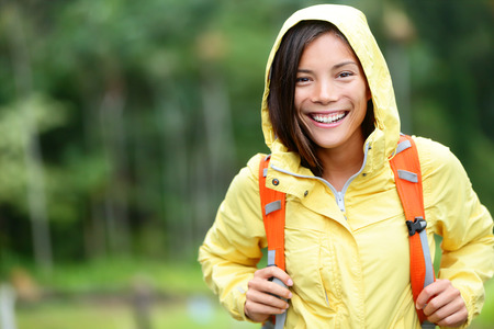 Rain woman hiking happy in forest. Female hiker portrait standing with backpack joyful on rainy day wearing yellow raincoat outside in nature forest by. Multi-ethnic Asian girl. photo