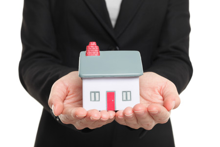 loaning: New Home and house owner concept. Woman holding a model house. Conceptual of home insurance and protection or real estate agent selling houses. Isolated on white .