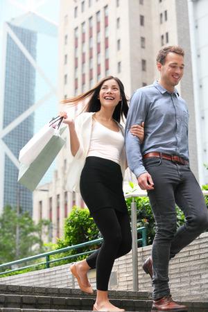 business asia: Acquisto delle coppie camminare felice di Hong Kong Central. Due giovani acquirenti di moda sorridente borse della spesa a piedi nella citt� insieme. Donna asiatica ed uomo caucasico.