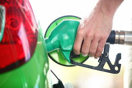 Benzinestation pomp. Man vullen benzine in groene auto houden mondstuk. Dichtbij.
