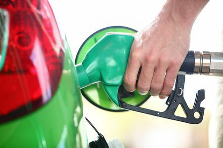 bomba de gasolina: La bomba de la gasolinera. Hombre llenar de combustible la gasolina en la boquilla de sujeción coche verde. Close up. Foto de archivo