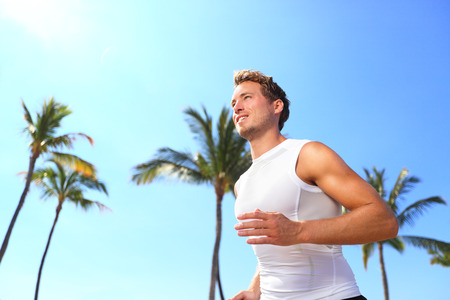 working model: Sport man running. Male athlete runner jogging in compression t-shirt top training on palm trees beach. Fit handsome male fitness model jogging alone training for marathon run. Man in his twenties. Stock Photo