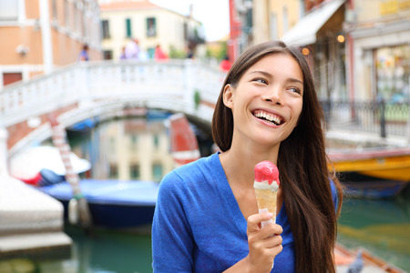 Woman in Venice, Italy eating Ice cream on vacation travel. Smiling happy Mixed race Asian Caucasian girl having fun eating italian gelato food outdoors during holidays in Venice, Italy, Europe. photo