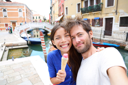 Couple in Venice, eating Ice cream taking selfie self-portrait photo on vacation travel in Italy. Smiling happy Asian woman and Caucasian man in love having fun eating italian gelato food outdoors. photo