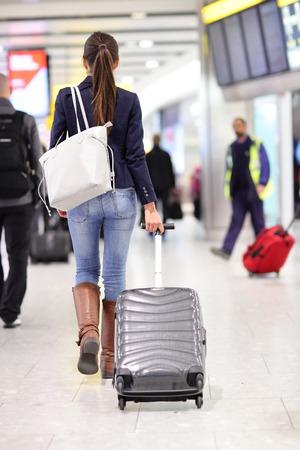 Cestování žena chodí na letišti se zavazadla zavazadel carry-na vozíku v plné délce těla. Mladá žena cestovatel na mezinárodní letištní brány jít cestování.