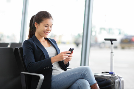 空港ターミナルで待っているゲートでスマート フォンでビジネスの女性。航空手荷物のスーツケースと一緒に座っている若いカジュアルな実業家と