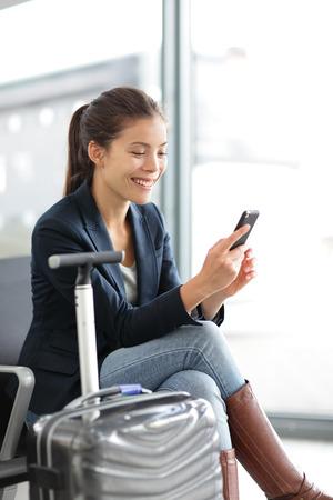 smart: Luchthaven vrouw op smartphone bij gate wachten in terminal. Vliegreizen concept met jonge casual zakenvrouw zitten met carry-on handbagage trolley. Mooie jonge gemengd ras vrouwelijke professionele