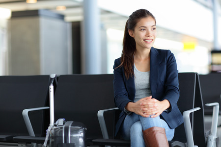 Passenger. Asian woman in airport waiting for air travel. Young business woman smiling sitting with travel suitcase trolley, in the waiting hall of the departure lounge of an international airport. Stock Photo