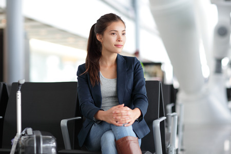 sit: Airport woman waiting in terminal. Air travel concept with young casual business woman sitting with carry-on hand luggage trolley in airport lounge. Beautiful young mixed race female professional