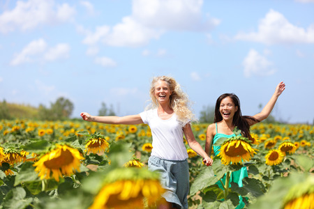 Two happy carefree young women running through field of sunflowers on a sunny summer day laughing and having fun with arms in the air. Beautiful young multiracial girlfriends, Asian and Caucasian girl photo
