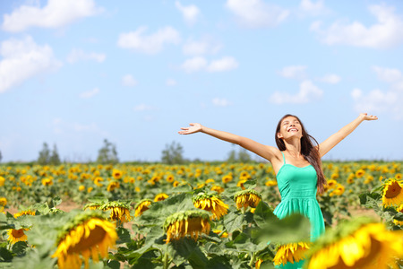 praising: Happy carefree summer girl in sunflower field in spring. Cheerful multiracial Asian Caucasian young woman joyful, smiling with arms raised up.
