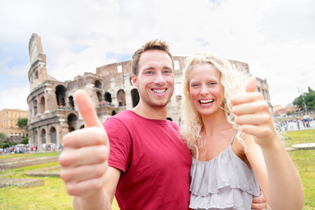 Happy Travel couple in Rome by Coliseum showing thumbs up hand sign looking at camera cheerful. Two tourists laughing having fun traveling in Italy. Beautiful blonde woman and man on holidays vacation photo