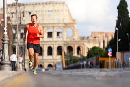 Running loper man door Colosseum, Rome, Italië. Mannelijke atleet training voor marathon joggen in de stad van Rome in de voorkant van het Colosseum in volle lichaamslengte. Fit mannelijke sport fitness model jogger in run buiten.