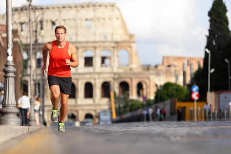 fitness model: Running runner man by Colosseum, Rome, Italy. Male athlete training for marathon jogging in city of Rome in front of Coliseum in full body length. Fit male sport fitness model jogger in run outside.